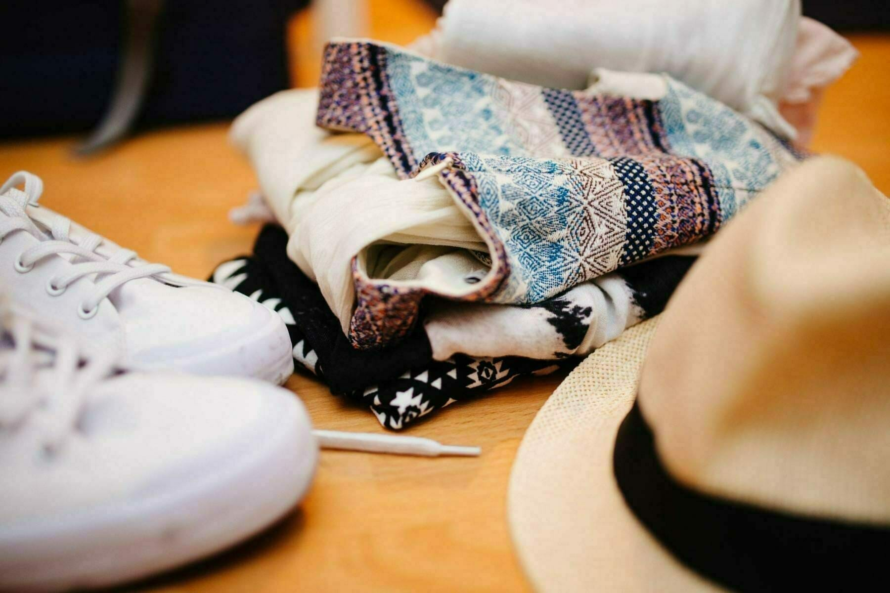 A close up of shoes, scarfs and a panama hat – all perfect to pack for your Italian vacation