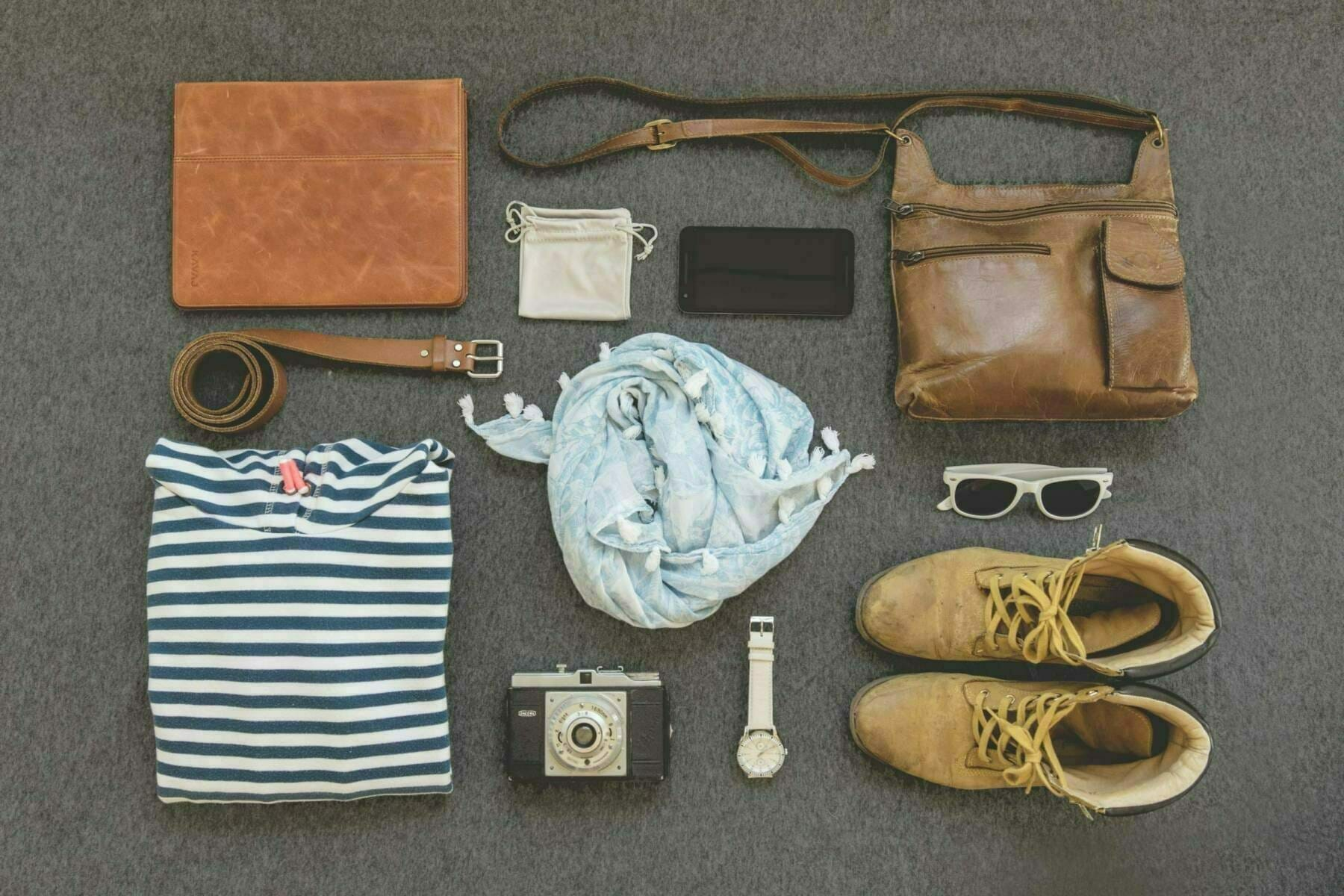 An above shot of the essentials to pack for your Italian vacation: leather purse and belt, sturdy shoes, sunglass, watch and camera. Change purse, t-shirt and versatile scarf.