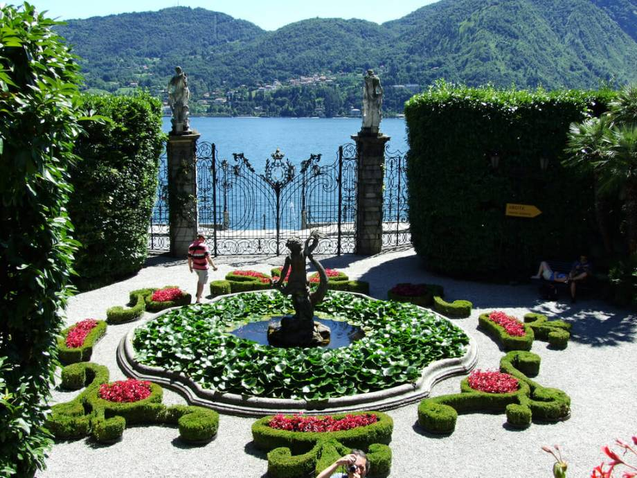 a fountain in Villa Carlotta encircled by decorative hedges overlooking Lake Como