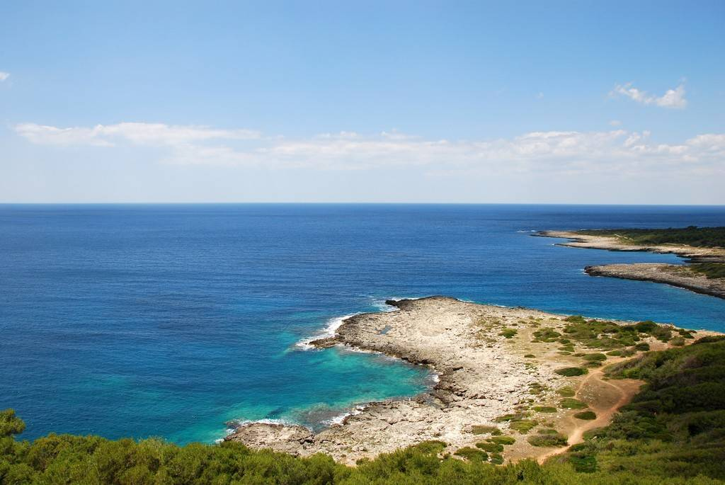 A wide view of the blue waters of Porto Selvaggio's bay, one of the best beaches in Puglia.