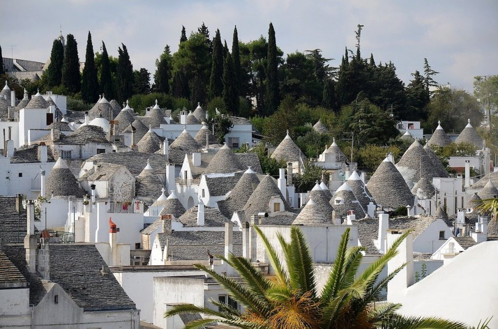 A village of the unique trulli houses in Puglia with white walls and conical roofs